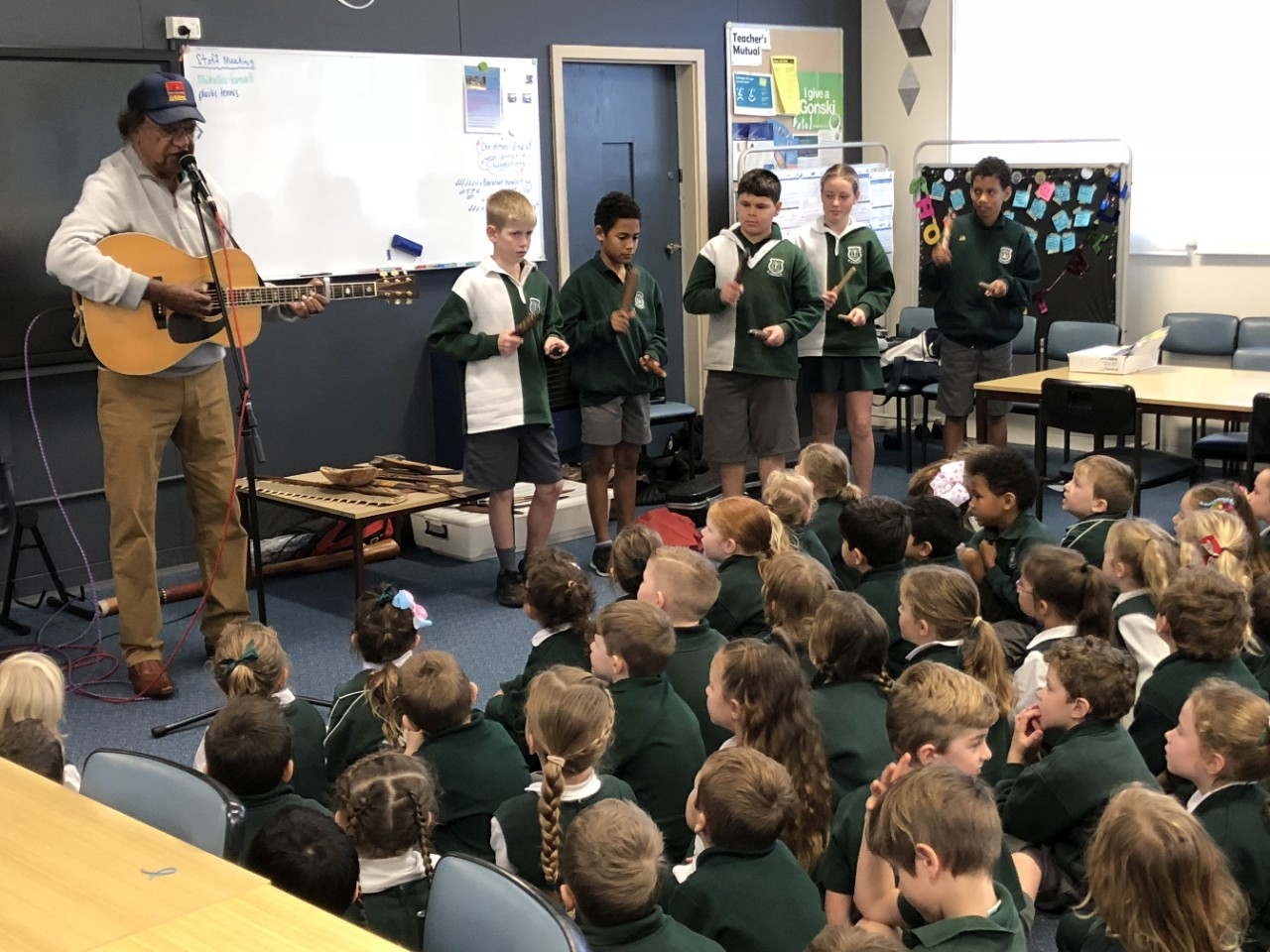 Aboriginal elder, Col Hardy playing guitar and singing to a group of kindergarten students